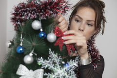 Young beautiful woman decorating Christmas tree Royalty Free Stock Images