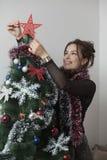 Young beautiful woman decorating Christmas tree Royalty Free Stock Photo