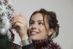 Young beautiful woman decorating Christmas tree Stock Photography