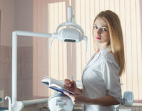 Young beautiful woman dentist. With a notebook and pen. Against. The background of the dental chair stock image
