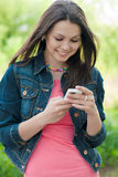 Young Beautiful woman & digital device outdoors Stock Image