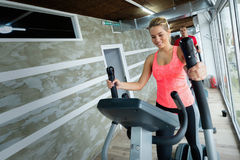 Young beautiful woman doing cardio in gym. Young beautiful women doing cardio exercise in gym elliptical trainer royalty free stock photos