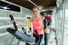 Young beautiful woman doing cardio in gym. Young beautiful women doing cardio exercise in gym elliptical trainer Royalty Free Stock Photography