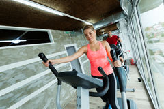 Young beautiful woman doing cardio in gym. Young beautiful women doing cardio exercise in gym elliptical trainer Royalty Free Stock Image