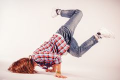 Young beautiful woman doing an element of breakdance dancing hip. Hop on a light background Stock Images