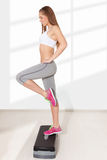 Young beautiful woman doing exercises with aerobic step Stock Image