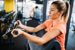 Young beautiful woman doing exercises for biceps. In gym Stock Images