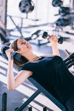 Young beautiful woman doing exercises with dumbbell in gym Royalty Free Stock Image