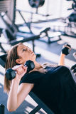 Young beautiful woman doing exercises with dumbbell in gym Royalty Free Stock Images