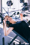 Young beautiful woman doing exercises with dumbbell in gym Royalty Free Stock Photo