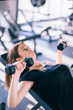 Young beautiful woman doing exercises with dumbbell in gym Stock Photo