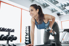 Young beautiful woman doing exercises with dumbbell in gym. Glad smiling girl is enjoying with her training process. She is working hard Royalty Free Stock Photo
