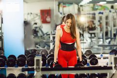 Young beautiful woman doing exercises with dumbbell in gym. Glad smiling girl is enjoying with her training process royalty free stock images