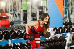 Young beautiful woman doing exercises with dumbbell in gym. Glad smiling girl is enjoying with her training process stock image