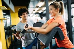 Young beautiful woman doing exercises with personal trainer. Young beautiful women doing exercises with personal trainer in gym Stock Photography