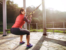 Young beautiful woman doing fitness training with suspension straps. Stock Image
