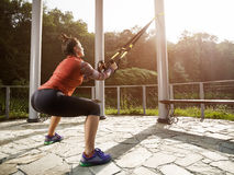 Young beautiful woman doing fitness training with suspension straps. Royalty Free Stock Images