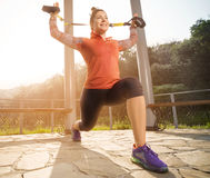 Young beautiful woman doing fitness training with suspension straps. Royalty Free Stock Photos