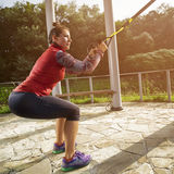 Young beautiful woman doing fitness training with suspension straps. Stock Images