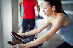 Young beautiful woman doing indoor biking exercise. Young beautiful women doing indoor biking exercise alone Stock Images