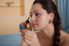 Young  beautiful woman doing makeup. Royalty Free Stock Photography