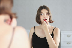 Young beautiful woman is doing makeup and looking in the mirror. Royalty Free Stock Images