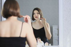 Young beautiful woman is doing makeup and looking in the mirror. Stock Images