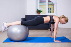 Young beautiful woman doing push up exercise with fit ball. At home royalty free stock photo