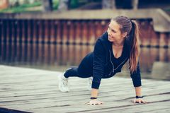 Young beautiful woman doing push up outdoors. Young beautiful woman doing push up before running in urban training workout royalty free stock image