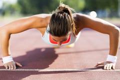 Young beautiful woman doing push-ups outdoors on a hot summer da Stock Photo