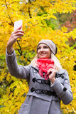 Young beautiful woman doing selfie outside at fall time Royalty Free Stock Images