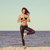 Young beautiful woman doing yoga on beach in black sport costume Stock Photo