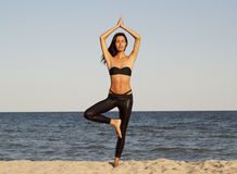 Young beautiful woman doing yoga on beach in black sport costume Stock Photography