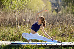 Young beautiful woman doing yoga in nature. Young woman doing yoga in nature. Female wearing sport clothes Royalty Free Stock Photography