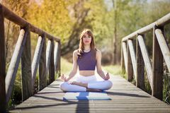 Young beautiful woman doing yoga in nature. Young woman doing yoga in nature. Female wearing sport clothes in lotus figure Royalty Free Stock Photography