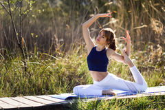Young beautiful woman doing yoga in nature. Young woman doing yoga in nature. Female wearing sport clothes in mermaid figure Stock Image