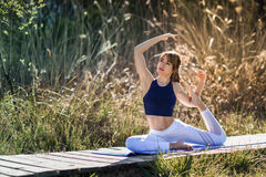 Young beautiful woman doing yoga in nature. Young woman doing yoga in nature. Female wearing sport clothes in mermaid figure Royalty Free Stock Image