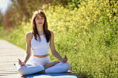 Young beautiful woman doing yoga in nature. Young woman doing yoga in nature. Female wearing white sport clothes in lotus figure Royalty Free Stock Photography