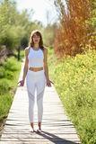 Young beautiful woman doing yoga in nature. Young woman doing yoga in nature. Female wearing white sport clothes on a wooden road Royalty Free Stock Image