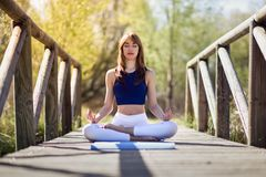 Young beautiful woman doing yoga in nature. Young woman doing yoga in nature. Female wearing sport clothes in lotus figure Stock Images
