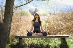 Young beautiful woman doing yoga in nature Stock Photos