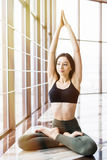 Young beautiful woman doing yoga padmasana in yoga studio. Sport health concept. royalty free stock image