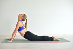 Young beautiful woman doing yoga poses indoor on grey background Stock Photography