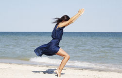 Young beautiful woman doing yoga at seaside in blue dress Stock Images