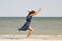 Young beautiful woman doing yoga at seaside in blue dress Royalty Free Stock Photography