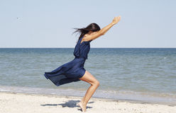 Young beautiful woman doing yoga at seaside in blue dress Stock Photos