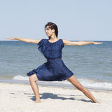 Young beautiful woman doing yoga at seaside in blue dress Royalty Free Stock Photo
