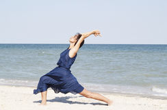 Young beautiful woman doing yoga at seaside in blue dress Royalty Free Stock Images
