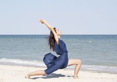 Young beautiful woman doing yoga at seaside in blue dress Stock Image