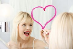 Young beautiful woman drawing big heart on mirror. Royalty Free Stock Images